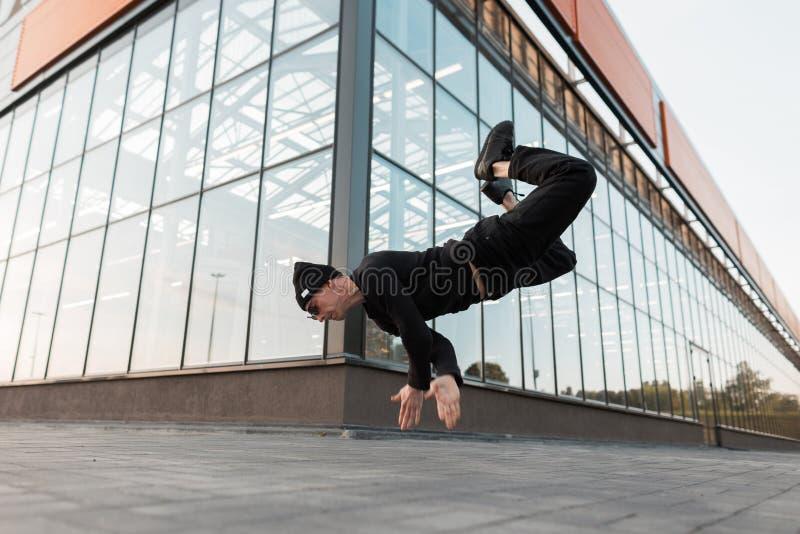 De atletische jonge mens in zwarte kleren in een modieuze hoed stelt in openlucht in de lucht dichtbij een glas modern gebouw Mod stock afbeeldingen