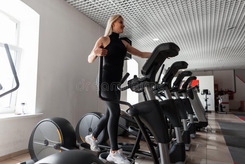 De atletische jonge mooie vrouw in een zwarte t-shirt in modieuze beenkappen in witte tennisschoenen leidt op een stepper simulat stock afbeelding