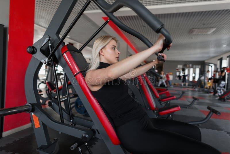 De atletische jonge vrouw in zwarte moderne sportkleding is bezig geweest met het zitten op de simulator in een geschiktheidsstud stock afbeelding