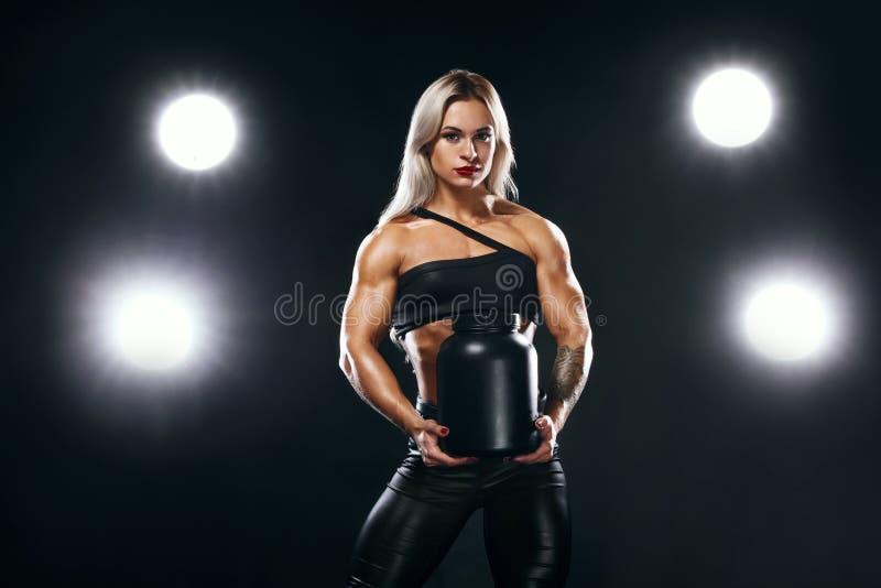 De atletische jonge vrouwenbodybuilder op stero?den heeft maaltijd bedriegen Fitness en sportconcept Voeding en het bodybuilding stock foto's