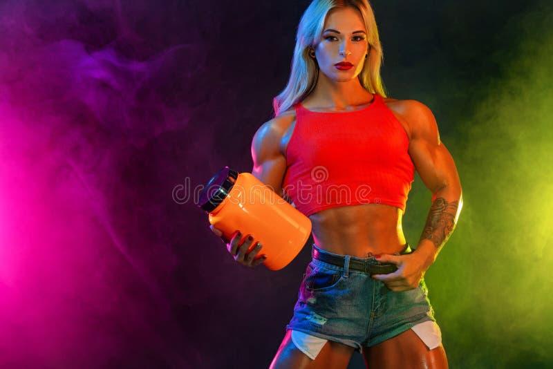 De atletische jonge vrouwenbodybuilder op steroïden weet hoe vaak u kunt hebben maaltijd bedriegen royalty-vrije stock afbeeldingen