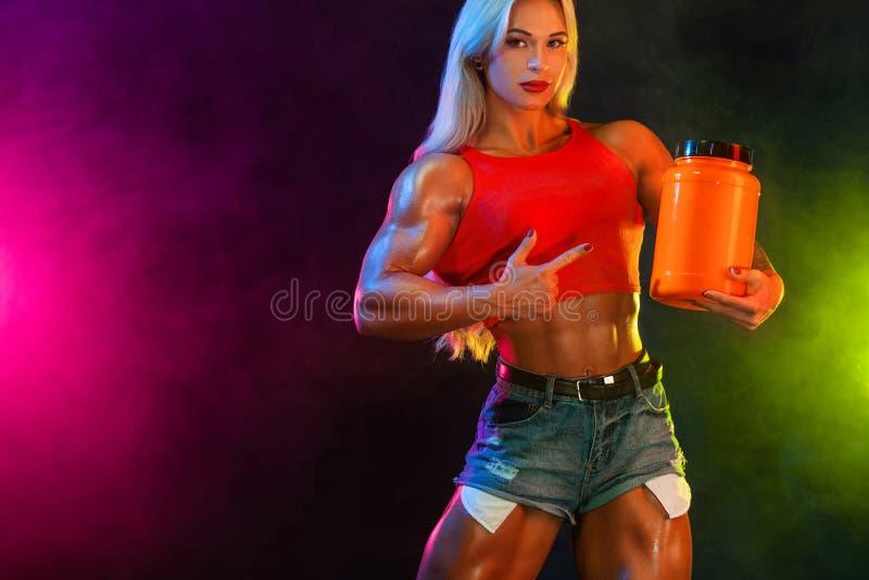 De atletische jonge vrouwenbodybuilder op stero?den weet hoe vaak u kunt hebben maaltijd bedriegen stock afbeelding