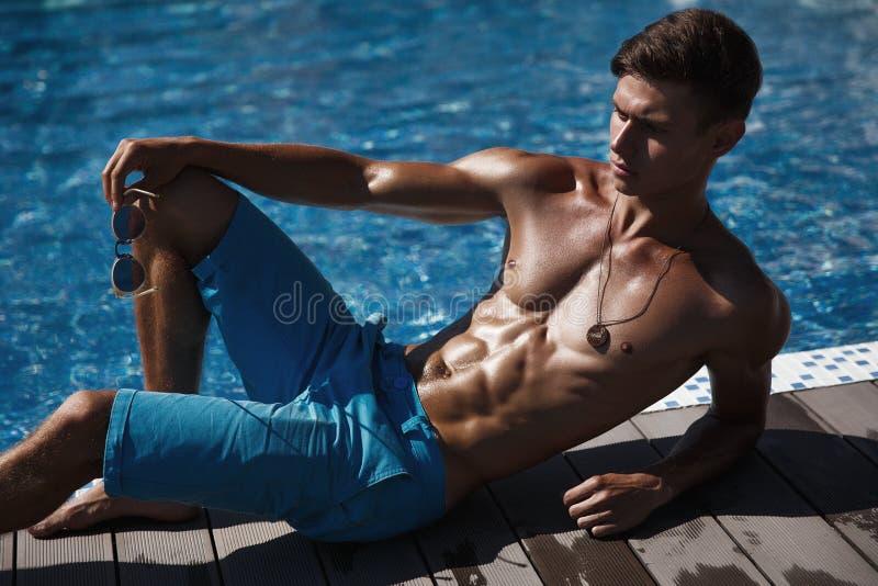 De atletische kerel met in zonnebril stelt dichtbij het zwembad royalty-vrije stock foto's