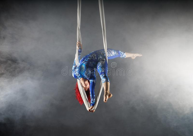 De atletische luchtcircuskunstenaar met roodharige in blauw kostuum die zich op één bevinden dient de luchtzijde in stock foto
