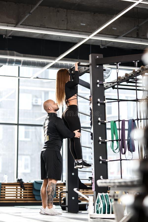 De atletische mens helpt jong slank meisje gekleed in zwarte soortenkleren te doen uittrekt op de bar in de gymnastiek royalty-vrije stock afbeeldingen