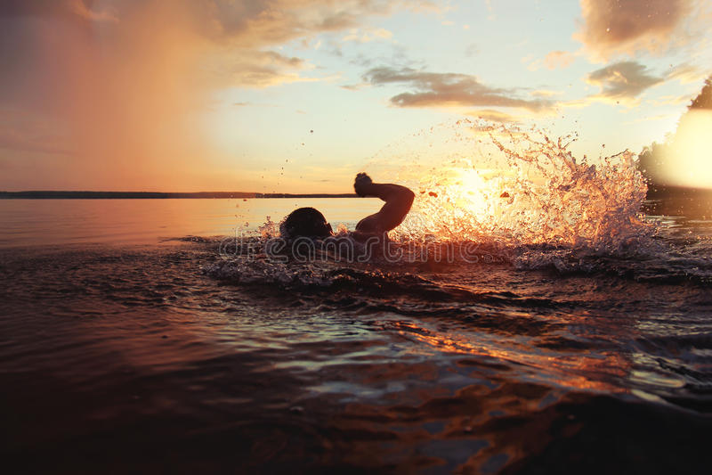 De atletische mens wordt opgeleid om in een meer bij zonsondergang te zwemmen Het vliegt heel wat water het bespatten stock fotografie