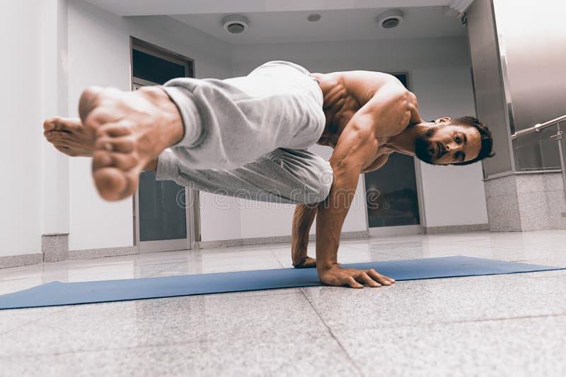 De atletische sterke mens die moeilijke yoga uitoefenen stelt stock afbeeldingen