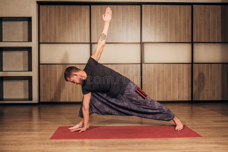 De atletische sterke mens die moeilijke yoga uitoefenen stelt royalty-vrije stock afbeeldingen