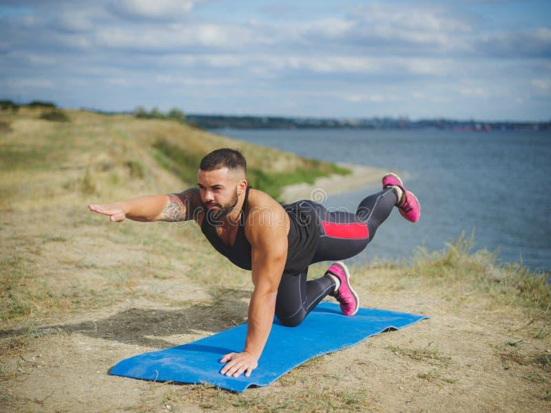 De atletische sterke mens die moeilijke yoga uitoefenen stelt in openlucht Jong mannetje, het praktizeren yoga in openlucht Buite stock afbeeldingen