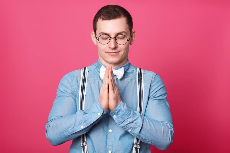 De atletische vreedzame jonge mensentribunes met gesloten ogen, zet palmen samen van zijn handen, bidt met glimlach op zijn gezic royalty-vrije stock afbeelding