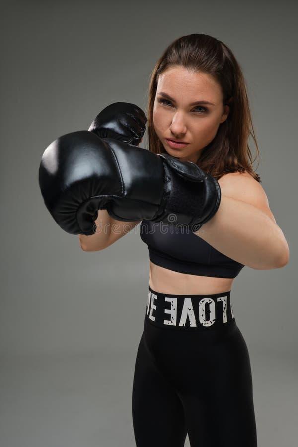De atletische vrouw in bokshandschoenen oefent karate in studio uit royalty-vrije stock afbeeldingen
