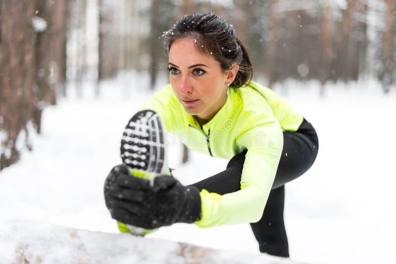 De atletische vrouw die haar uitrekken verlamt, benenoefening opleidingsgeschiktheid in openlucht vóór training stock afbeeldingen