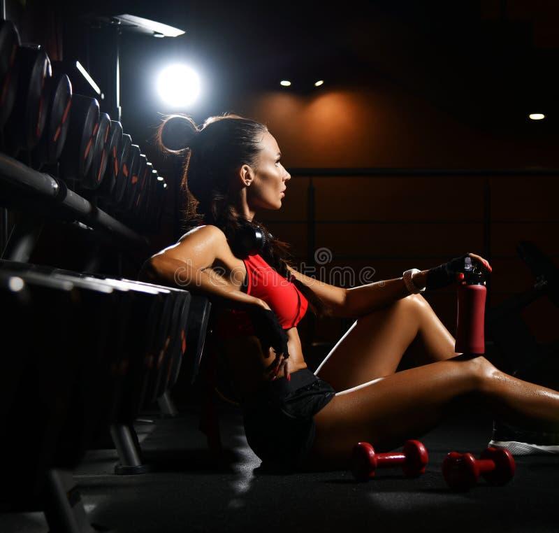 De atletische vrouw zit bij tribune met domoren tijdens de onderbreking in geschiktheidscentrum Dieet en gewichtsverliesconcept royalty-vrije stock afbeeldingen