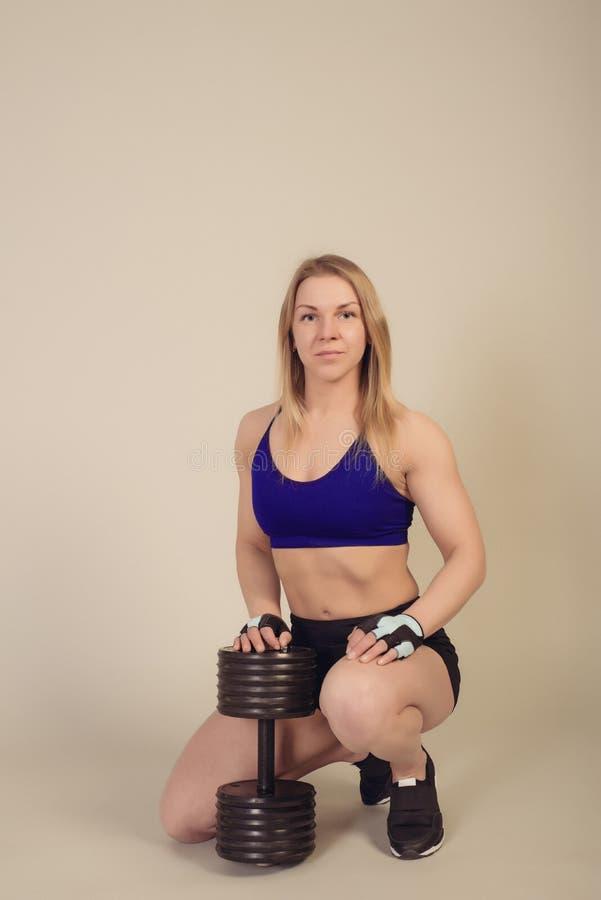 De atletische vrouwenbodybuilder zit met een zware domoor royalty-vrije stock afbeelding