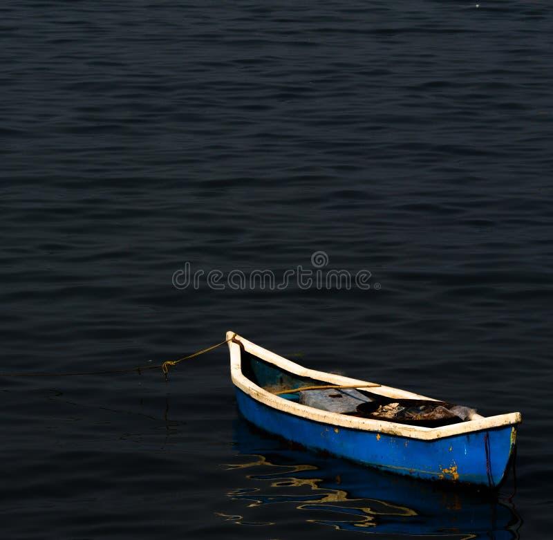 ` De ` au repos - un bateau bleu tout seulement dans l'apaisement et les eaux de mer sereines photos libres de droits