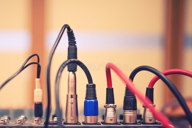 De audiohefboom en de draden verbonden met audiomixer, het materiaal van muziekdj bij overleg, festival of partij stock foto
