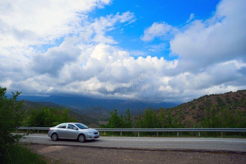 De auto berijdt op de manier aan de bergen stock afbeelding