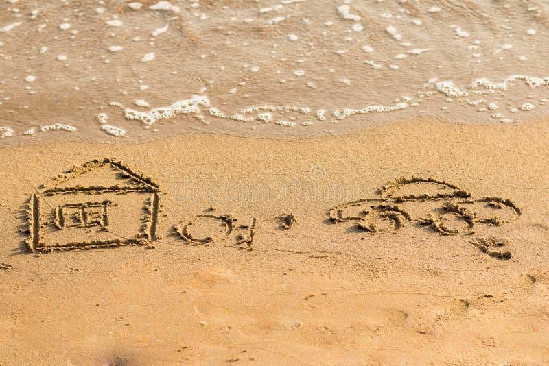 De auto is dichtbij het huis op een zandig gouden overzees strand met de hand wordt getrokken dat concept risico in vastgoedfinan stock afbeeldingen