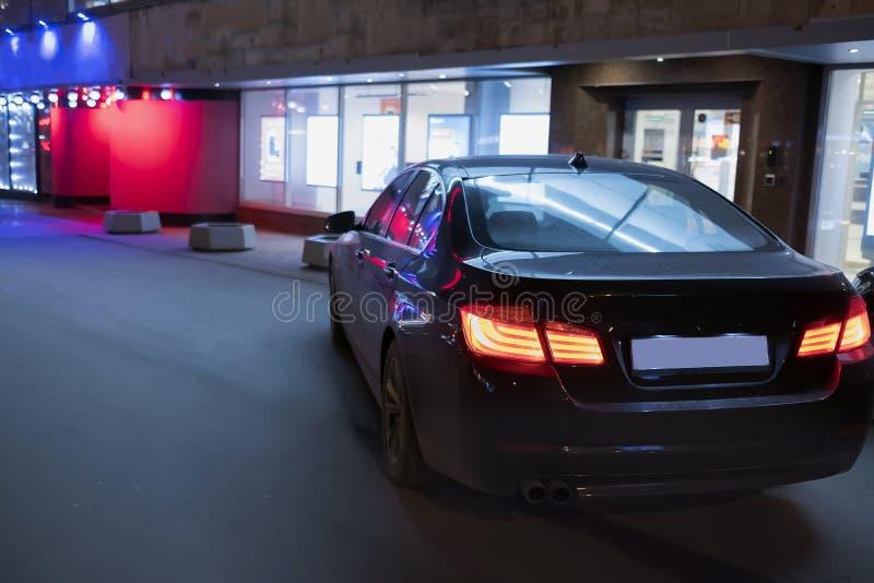 De auto, die zich naast de opslag, bij de nacht bevinden royalty-vrije stock afbeelding