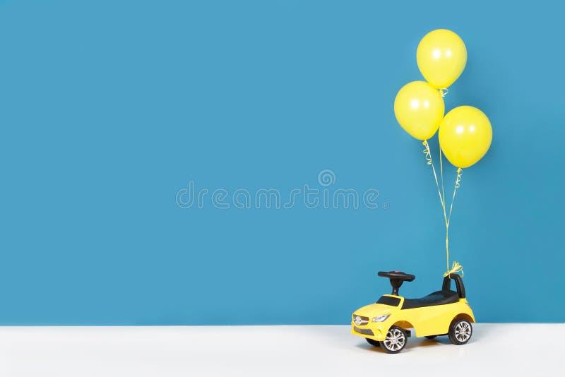 De auto en de ballons van gele kinderen stock foto