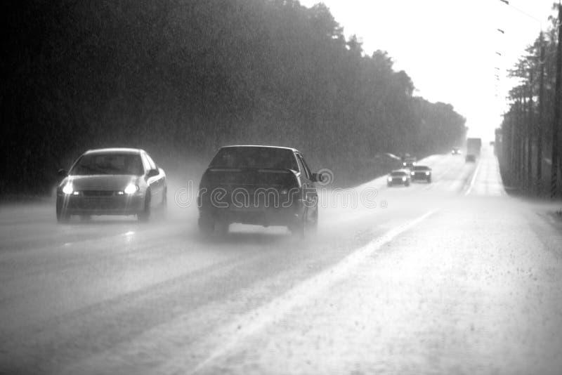 De auto gaat op de weg in een stortbui royalty-vrije stock afbeeldingen