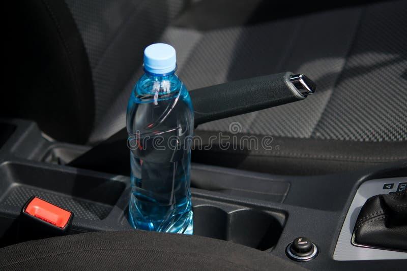 In de auto in de kophouder is er een fles water, voor de bestuurder stock afbeelding