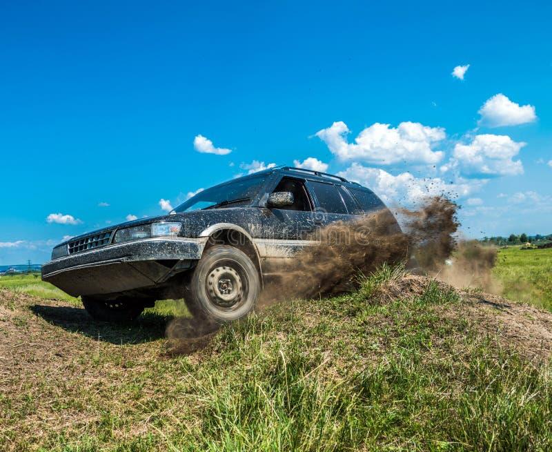De auto op de helling wordt geleund, het wiel was van de grond, die in de lucht, de aardevliegen hangen die stock fotografie