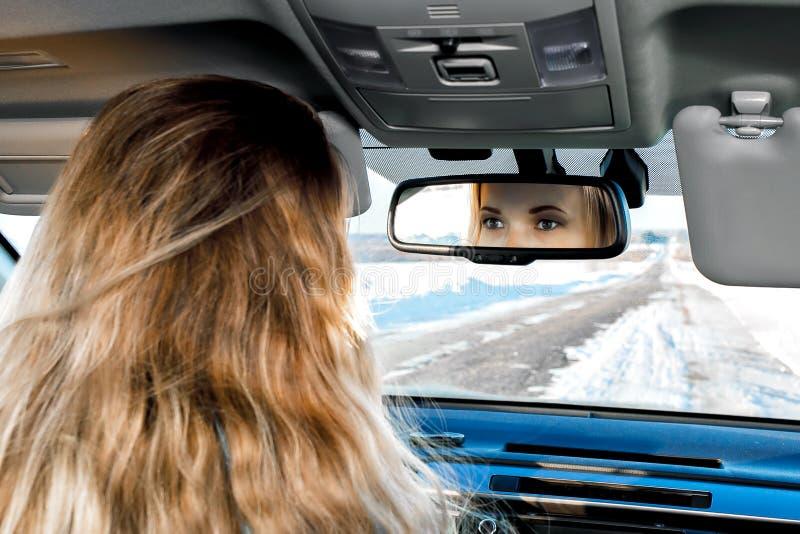 In de auto op de de winterweg kunt u de ogen in de achteruitkijkspiegel van de zitting van het blondemeisje achter het wiel zien royalty-vrije stock foto's