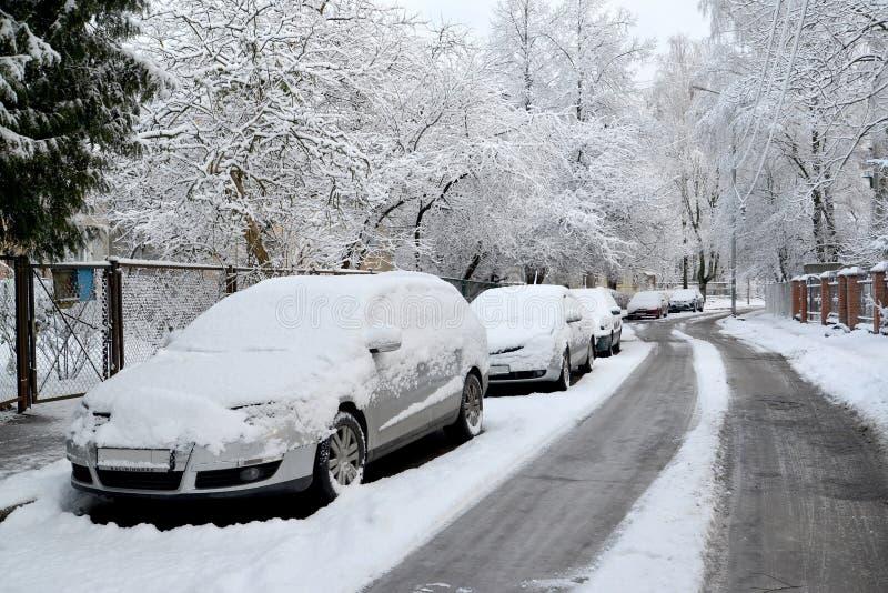 De auto's die met sneeuwtribune op de straat van Kaliningrad worden opgevuld stock afbeelding