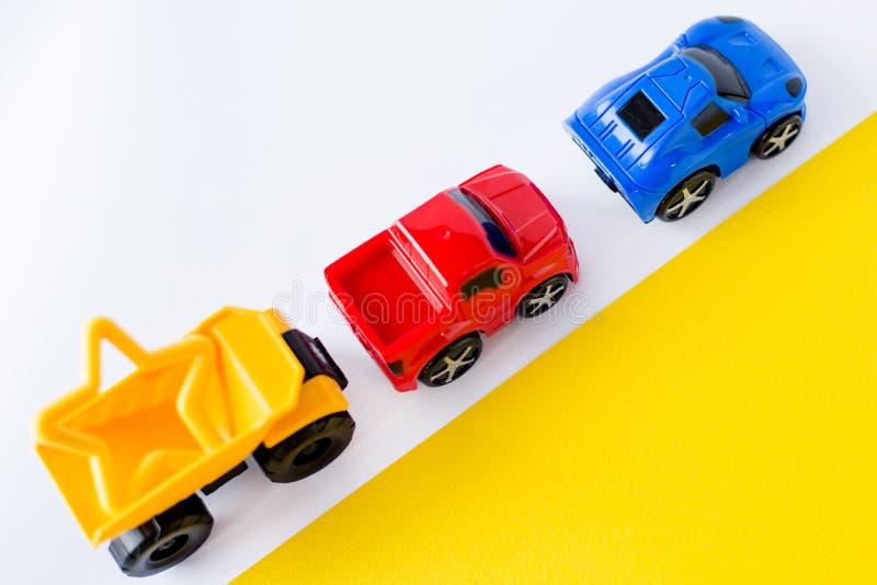 De auto's van het jonge geitjesspeelgoed op witte en gele achtergrond Hoogste mening Vlak leg Voor tekst Grappige kat en muis stock afbeeldingen