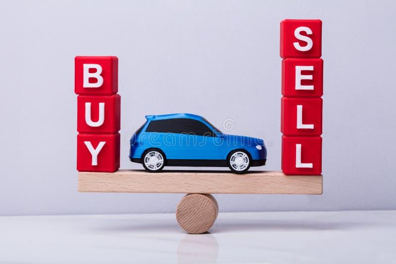 De auto tussen en koopt en verkoopt het In evenwicht brengen op Geschommel royalty-vrije stock foto's
