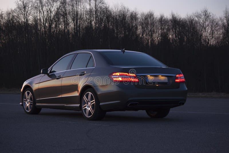 De auto van de luxe op de avondweg stock afbeeldingen