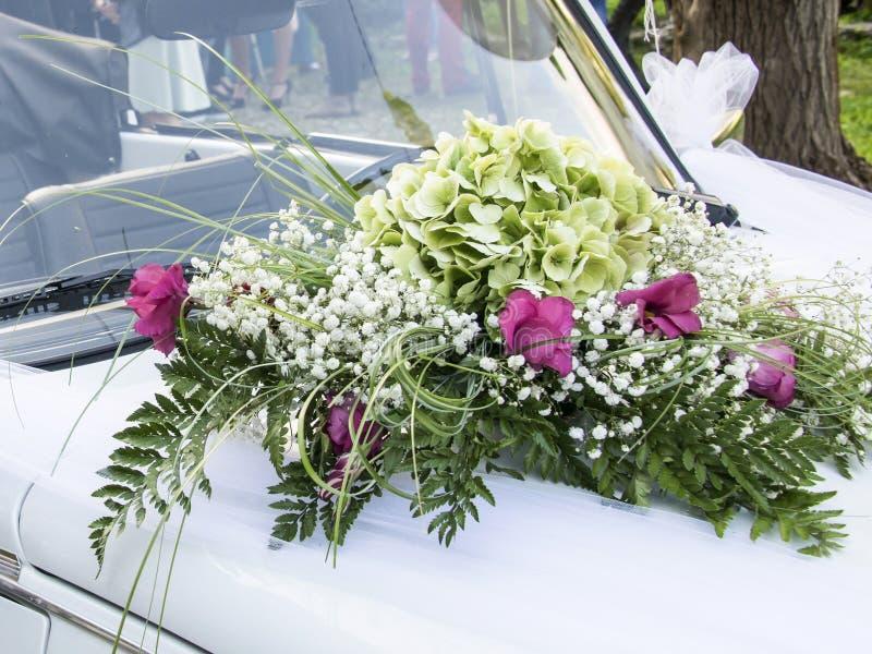 De auto van het huwelijk die met bloemen wordt verfraaid