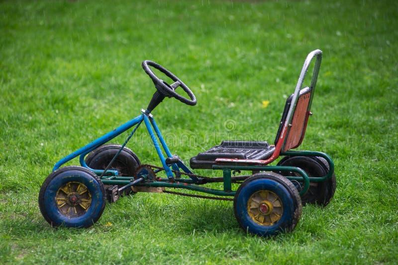 De auto van oude kinderen, die zich op groen gras in de regen bevinden isoleer royalty-vrije stock foto