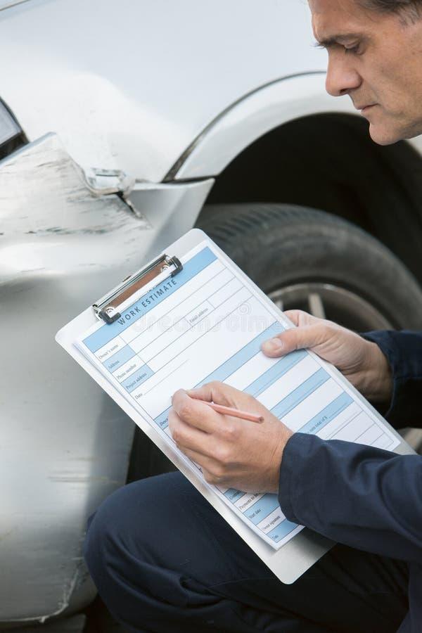 De autoauto van Workshop Mechanische Inspecting Damage To en het Invullen van R stock fotografie