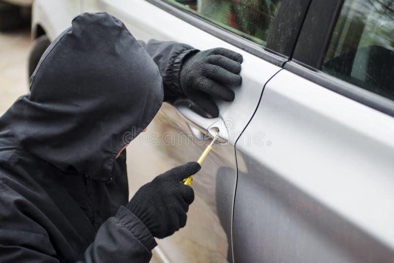 De autodief in actie, een mens in een kap breekt een deur van de schroevedraaierauto De man kleedde zich in het zwarte proberen o royalty-vrije stock foto's