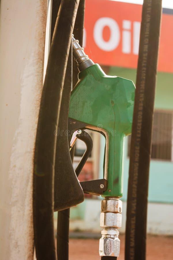 De automaat van de stookoliebenzine bij benzinebenzinestation De pijp van de holdingsbrandstof om benzine voor auto bij te tanken royalty-vrije stock afbeelding
