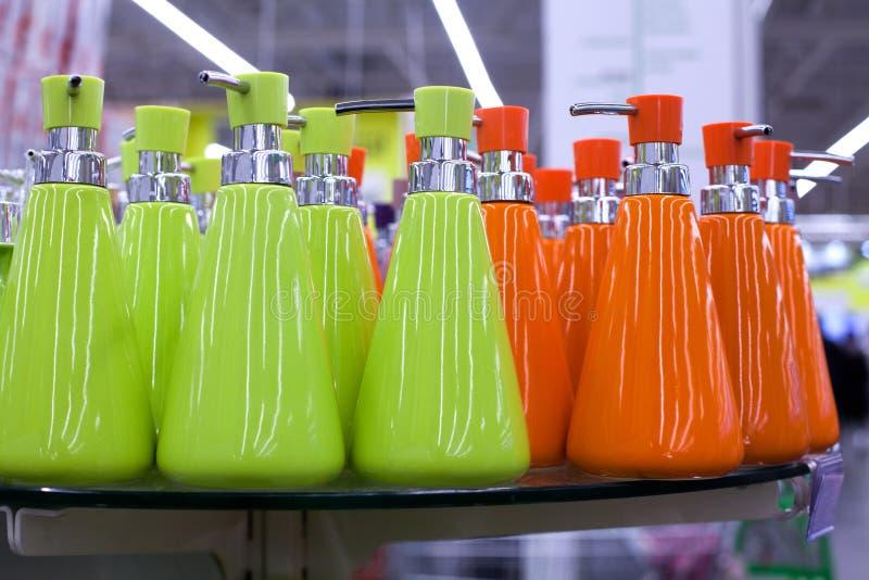 De automaat van de zeepschotel voor vloeibare zeep, badkamers ceramische toebehoren in groene en oranje kleuren op glas schort in royalty-vrije stock afbeeldingen