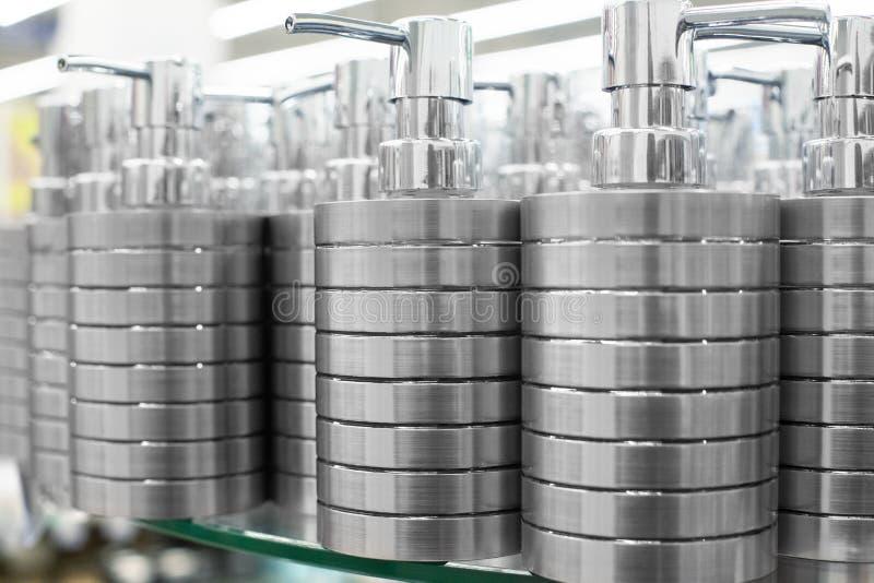 De automaat van de zeepschotel voor vloeibare zeep, de toebehoren van het badkamersmetaal op glas schort in opslag dichte omhoogg stock foto's