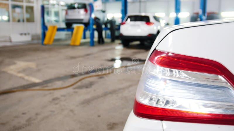 De automobiele dienst - de werktuigkundigen die opgeheven auto controleren, defocused achtergrond stock fotografie