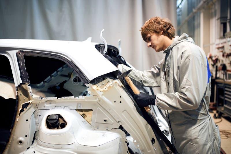 De autoreparatiearbeider vlakt en richt de auto van het metaallichaam op hamer in garage af stock afbeelding