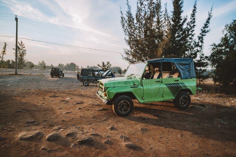 De Autovoertuig van leger Groen Off Road Klaar voor Avontuur op Zandduinen in Mui Ne, Vietnam op Woestijnlandschap en Blauwe Heme royalty-vrije stock foto's