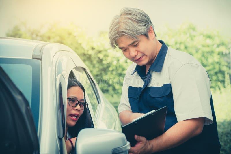 De autowerktuigkundige beschrijft de details van de autoinspectie Voor vrouwen die voor begrip alvorens te herstellen bezitten royalty-vrije stock afbeeldingen