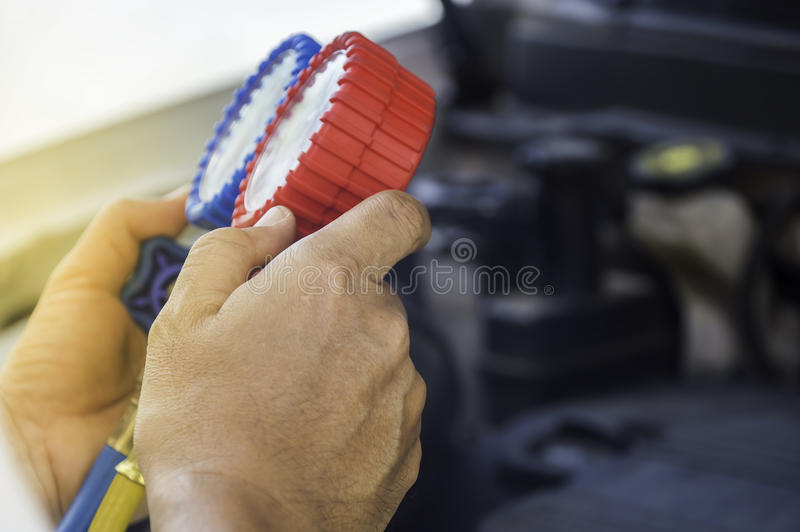 De autowerktuigkundige gebruikt een drukmaat op de luchtcompressor, vloeistof stock afbeelding