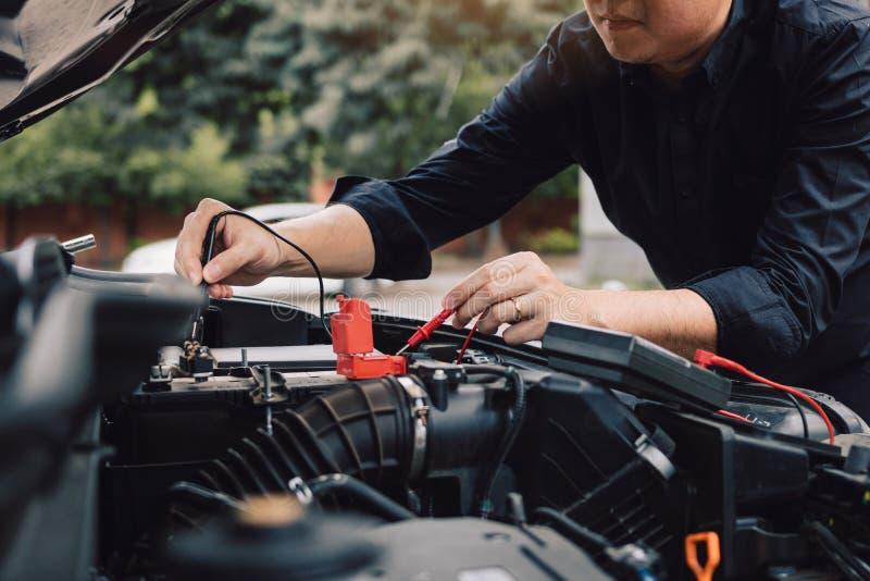 De autowerktuigkundige gebruikt de meter van de autobatterij om diverse waarden te meten en het te analyseren royalty-vrije stock fotografie