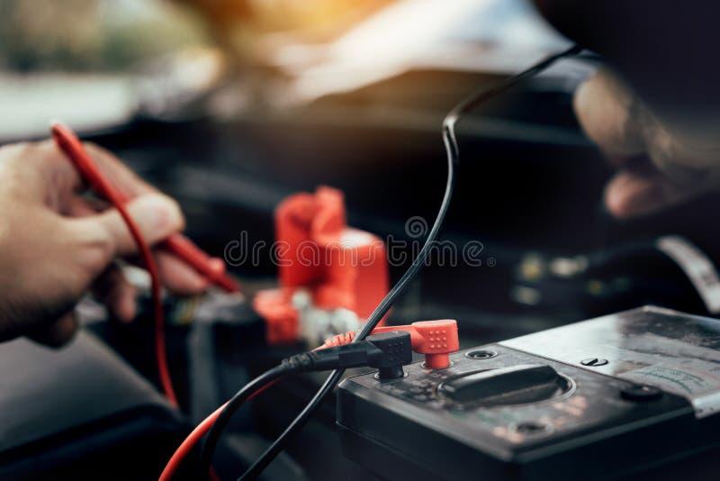 De autowerktuigkundige gebruikt de meter van de autobatterij om diverse waarden te meten en het te analyseren stock afbeeldingen