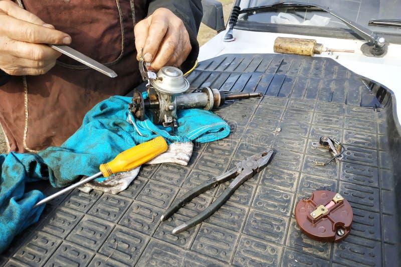 De autowerktuigkundige voert reparatie van de verdeler van ontsteking van de oude auto uit stock afbeeldingen