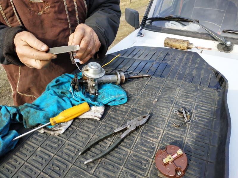 De autowerktuigkundige voert reparatie van de verdeler van ontsteking van de oude auto uit stock foto's
