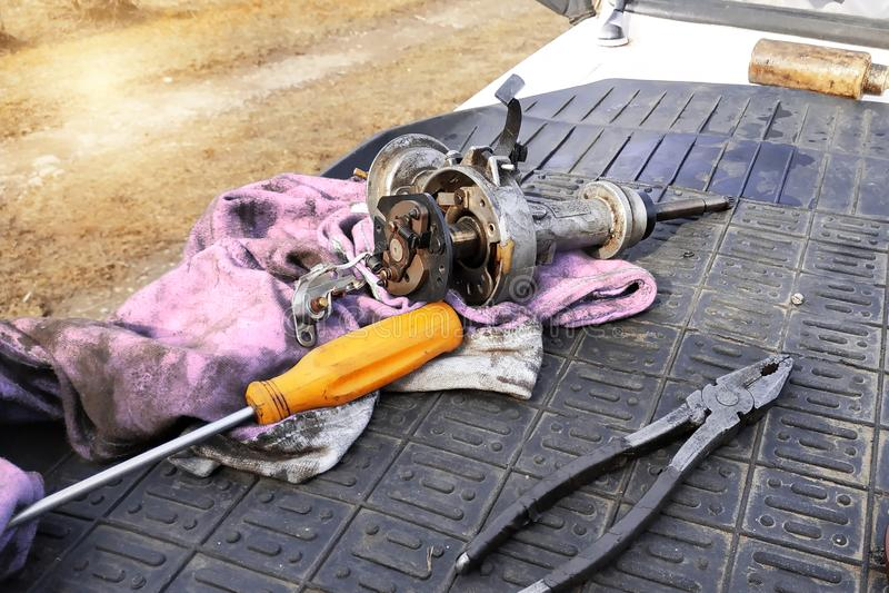 De autowerktuigkundige voert reparatie van de verdeler van ontsteking van de oude VAZ-merkauto uit stock foto