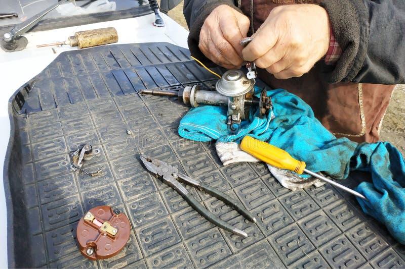 De autowerktuigkundige voert reparatie van de verdeler van ontsteking van de oude VAZ-merkauto uit royalty-vrije stock foto